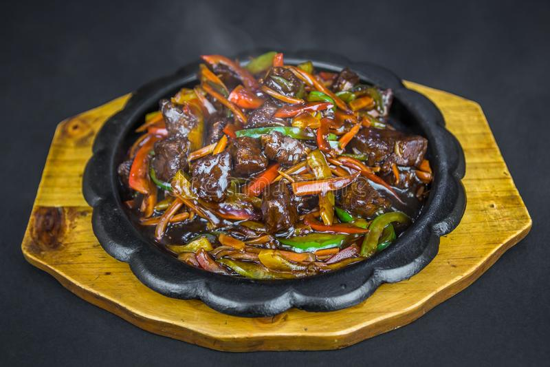 Chinese food. Szechuan beef in spicy sauce with paprika and carrot on the wooden board. Black background royalty free stock image