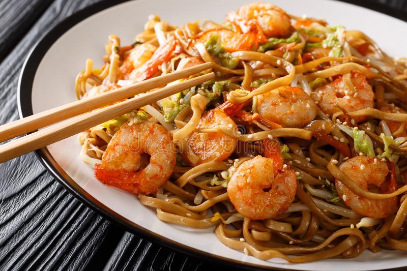 Chinese food chow mein noodles with shrimp, vegetables and sesame seeds close-up on a plate. horizontal stock photos