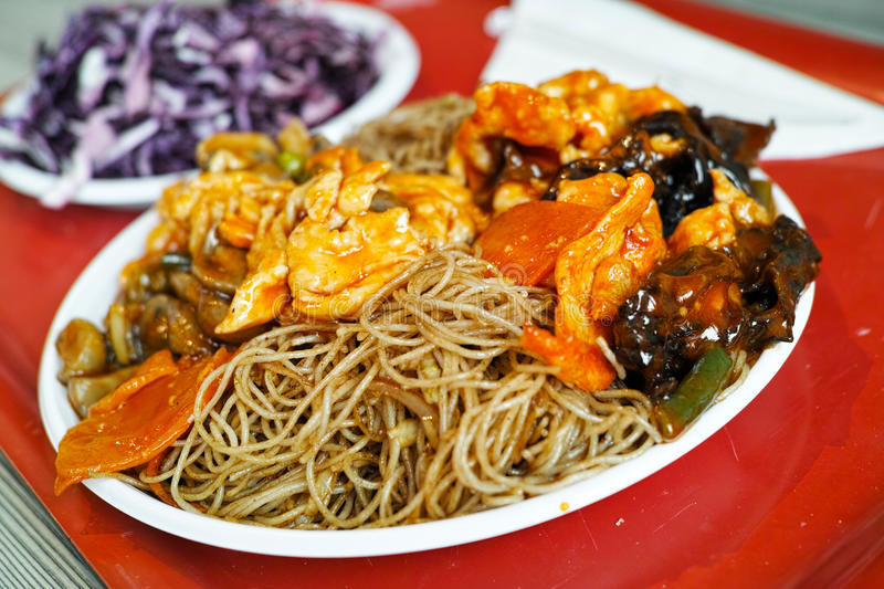 Chinese food details. Chinese food with rice noodles, mushrooms and chicken meat on white plastic plate against red background royalty free stock photography