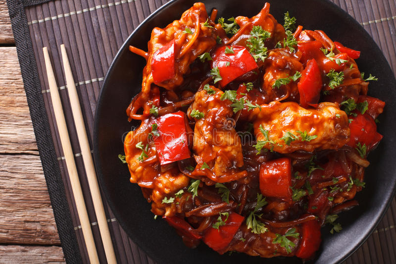 Chinese food: pork in sauce with vegetables on a plate. Horizontal top view stock photo