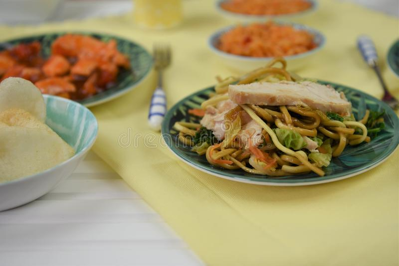 Chinese food served on a table with traditional dishes. A table layout with traditional Chinese food of fresh crisp crunchy prawn crackers in a dish and with royalty free stock image