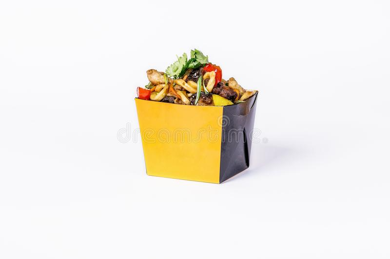 Chinese food. Stir fry noodles with chicken vegetables and mushrooms on white background. In take away wok noodles box.  royalty free stock photos