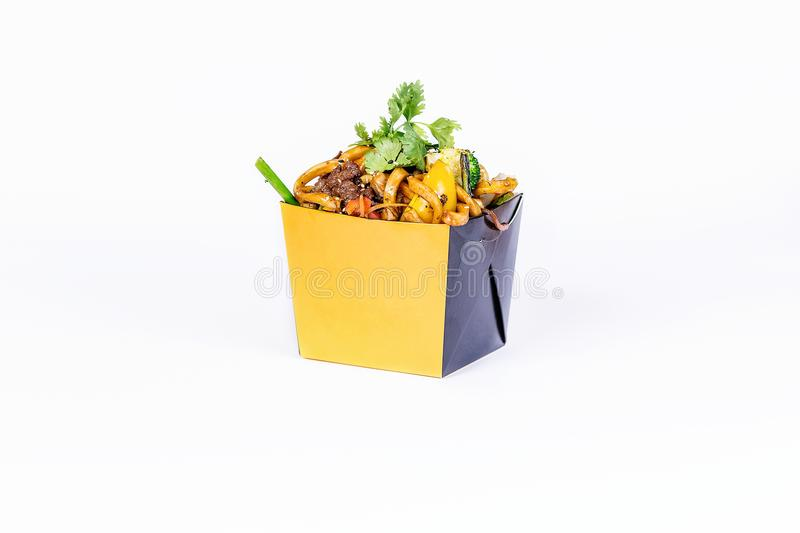 Chinese food. Stir fry noodles with meat on white background. In take away wok noodles box.  stock images