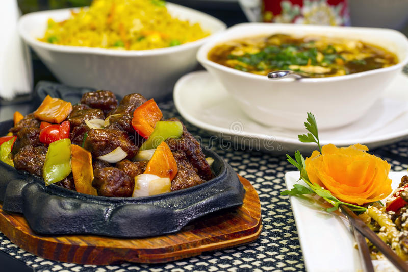 Chinese food. Various Chinese food dishes on table, including soup, rice with vegetables and beef meat. Selective focus royalty free stock image