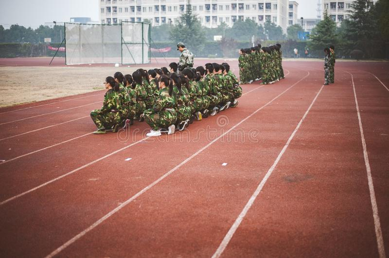 Chinese freshmen college students during military training. Chinese freshmen college students are sitting still during military training at school. view from the royalty free stock photos