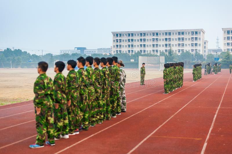 Chinese freshmen college students during military training. Chinese freshmen college students are standing stand still during military training at school. view stock photo