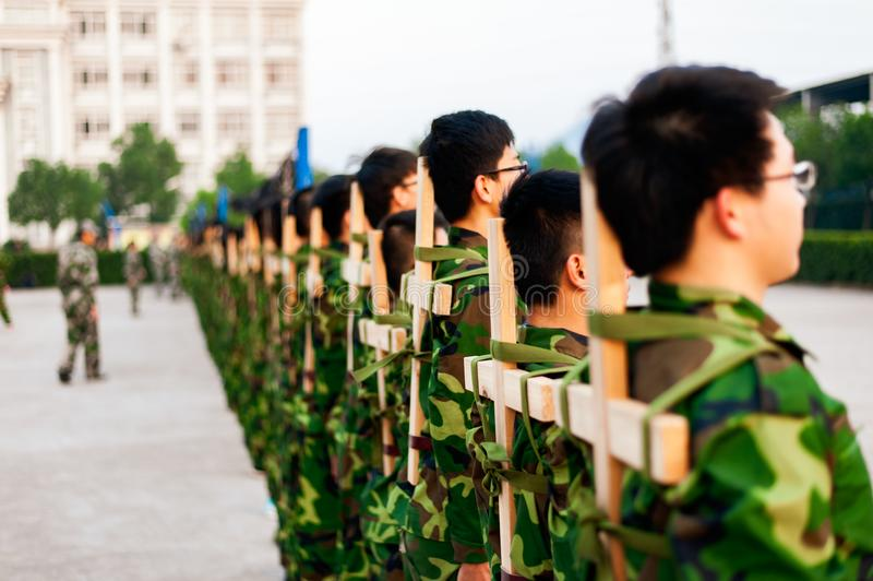 Chinese freshmen college students at military training. Chinese freshmen college students are standing stand still during military training at school with wooden royalty free stock photo