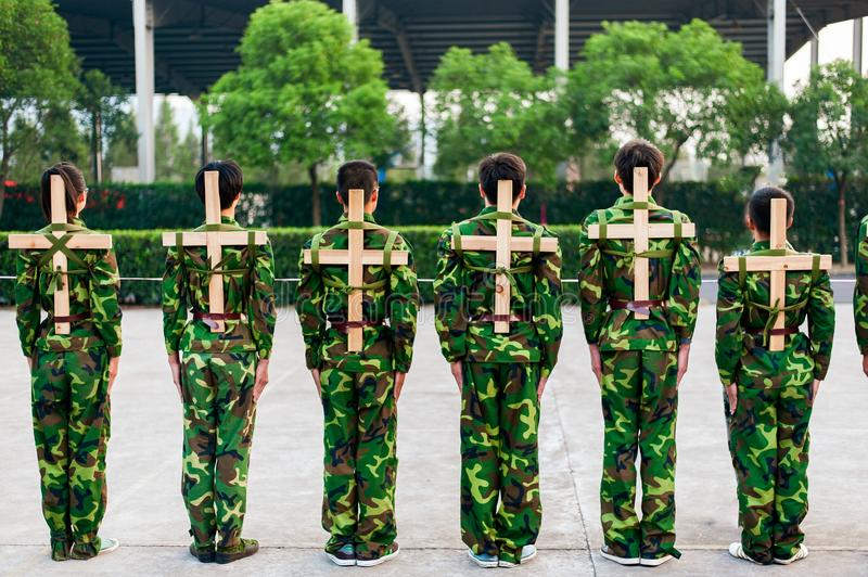 Chinese freshmen college students at military training. Chinese freshmen college students are standing stand still during military training at school with wooden stock photo