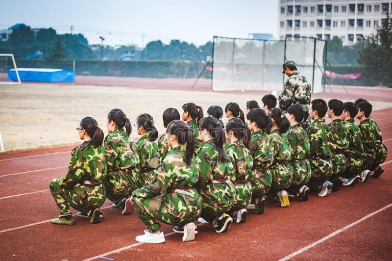 Chinese freshmen college students during military training. Chinese freshmen college students are sitting still during military training at school. view from the stock photo
