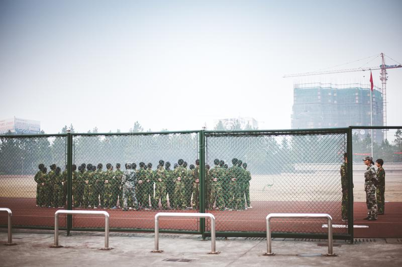 Chinese freshmen college students during military training. Chinese freshmen college students are standing stand still during military training at school. view stock photography