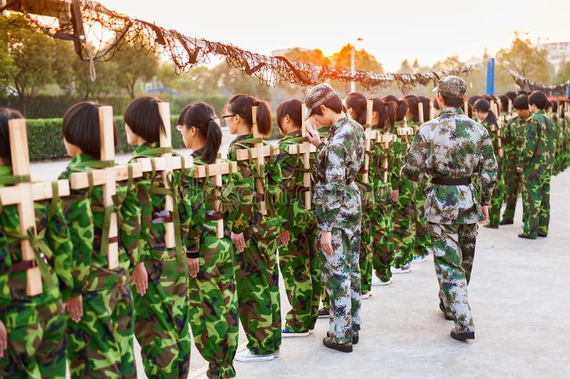 Chinese freshmen college students at military training. Chinese freshmen college students are standing stand still during military training at school with wooden royalty free stock photography