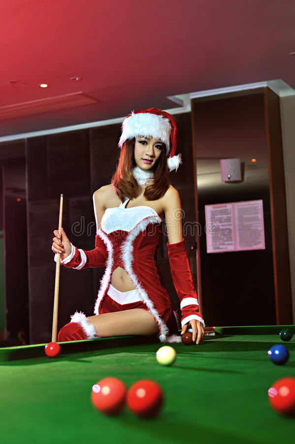 A Chinese girl dressed in Christmas costumes. Play billiards, to celebrate Christmas, has become a Christmas baby royalty free stock photography