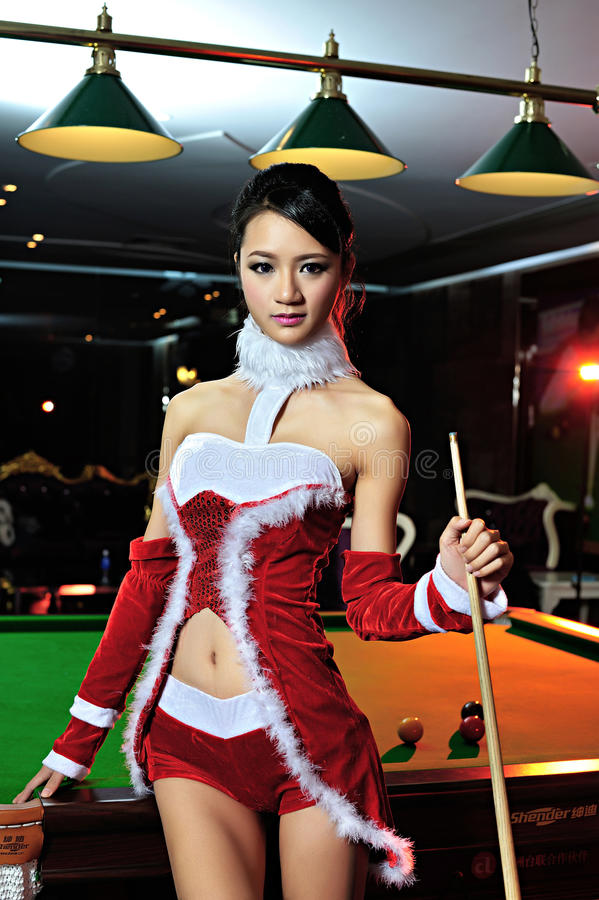 A Chinese girl dressed in Christmas costumes. Play billiards, to celebrate Christmas, has become a Christmas baby stock image