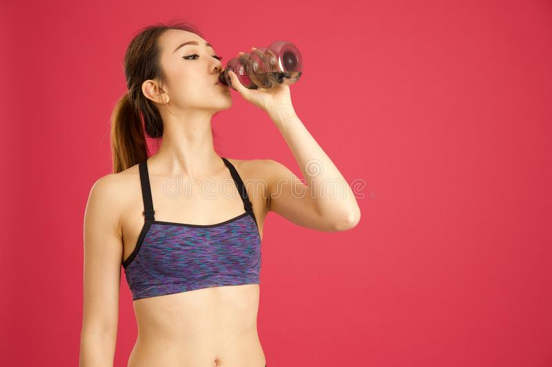 Chinese girl drinking water out of bottle in pink background royalty free stock photo