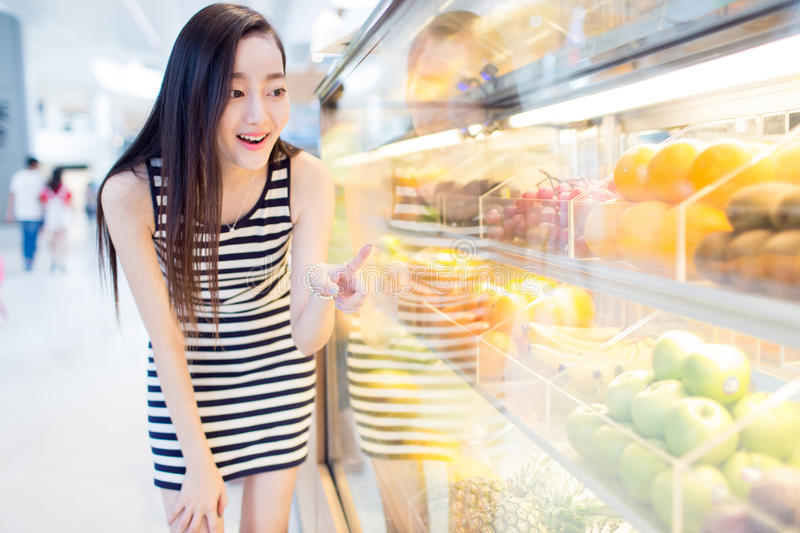 Chinese girl and fresh fruit. Beautiful chinese girl, in the shopping center supermarket, buy her favorite fruits and vegetables royalty free stock photography