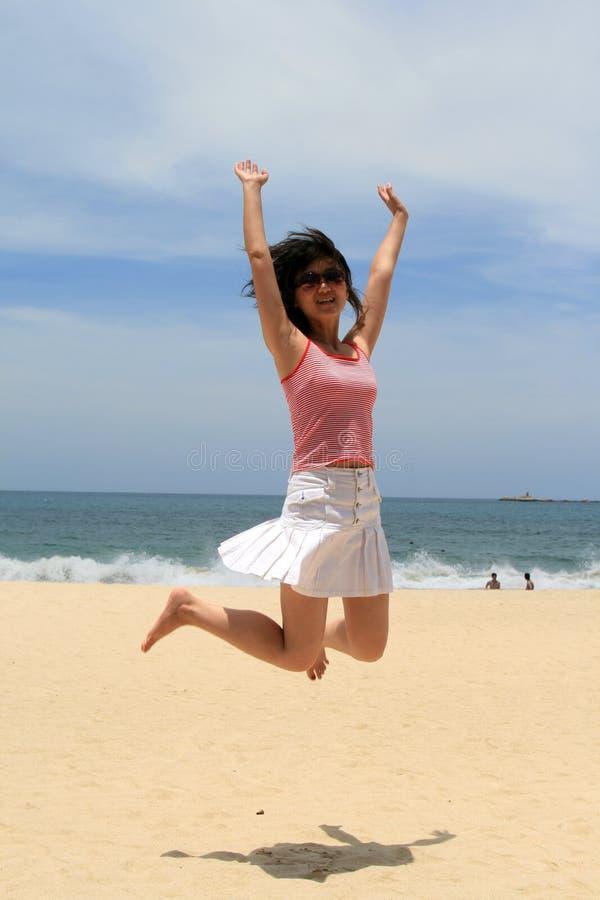 Chinese girl jump at beach stock image