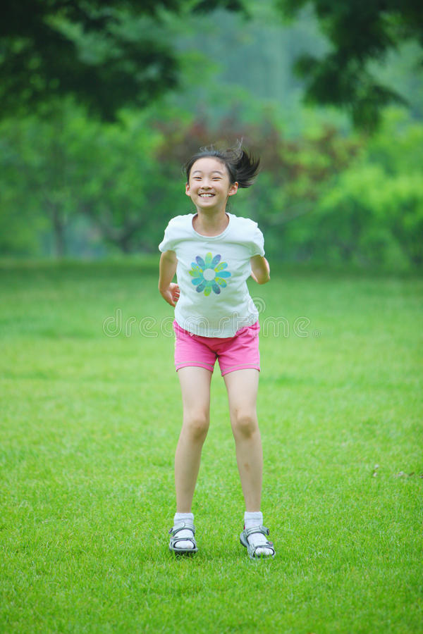 Chinese girl jump on lawn royalty free stock photo