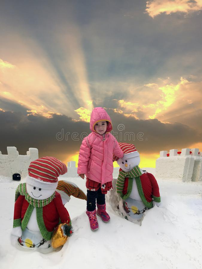 Happy girl, happy snowman, happy frozen. Chinese girl playing with her snowmen in snowy field, sunburst sky, merry Christmas and happy new year scenery stock photography