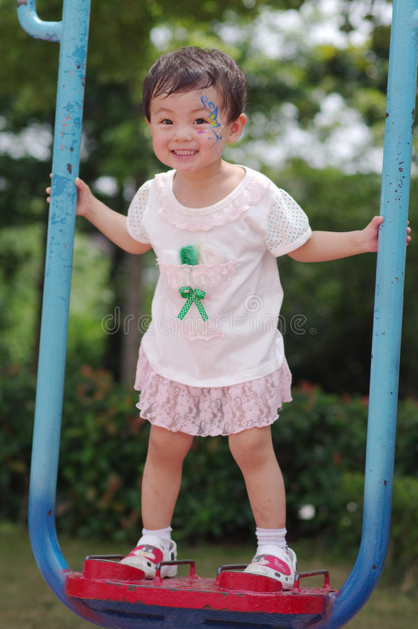 Chinese girl playing on a swing stock image