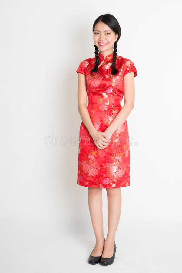 Chinese girl. Portrait of full length Asian Chinese female, in traditional red cheongsam standing on plain background royalty free stock image