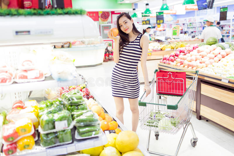 Chinese girl in the selection of fruit. Beautiful chinese girl, in the shopping center supermarket, buy her favorite fruits and vegetables stock photos