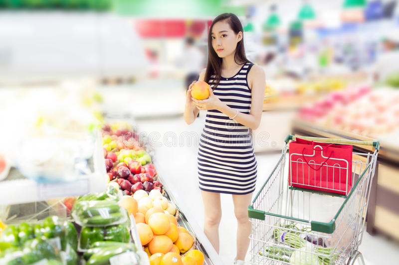 Chinese girl in the selection of fruit. Beautiful chinese girl, in the shopping center supermarket, buy her favorite fruits and vegetables royalty free stock photos