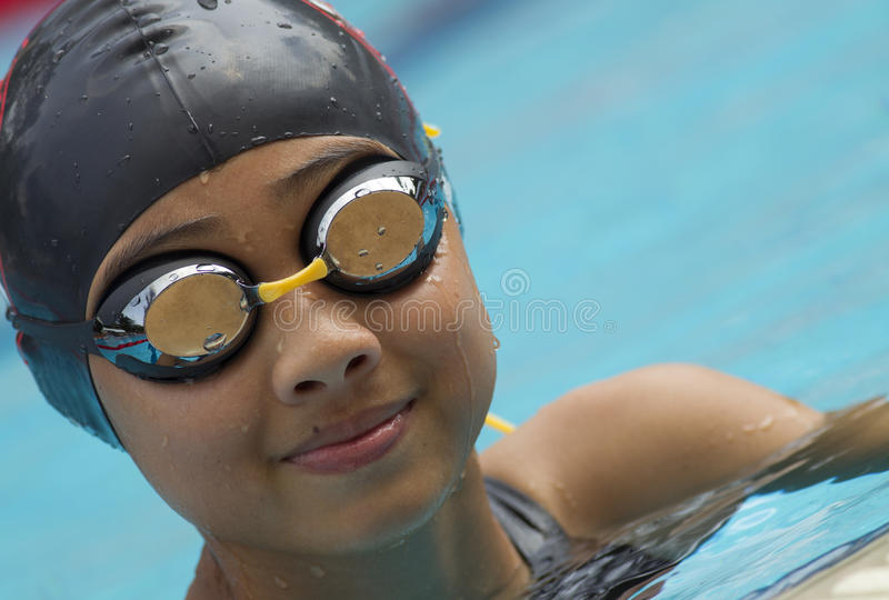 Chinese girl in swim cap smiles. Young chinese girl wearing black swim cap smiles happily in a swimming pool stock photography