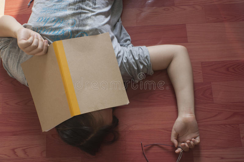 The chinese girl is tired to look at the notbook and fall asleep on the floor stock photos