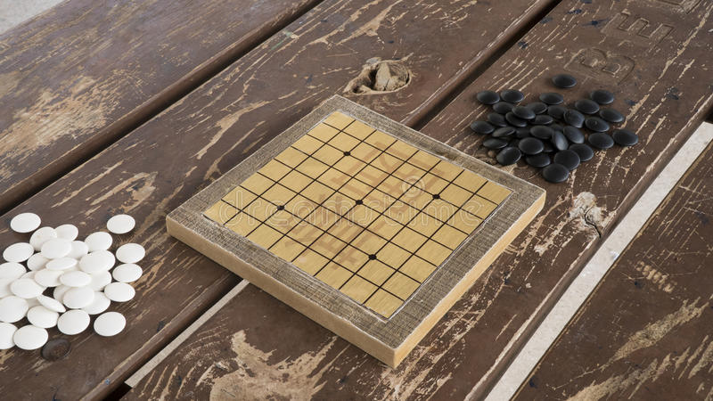 Chinese Go or Weiqi board game. Black and white stones and hand made small board. royalty free stock photography