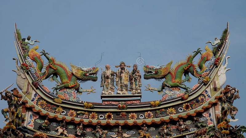 Chinese god sculpture on roof top of chinese temple stock images