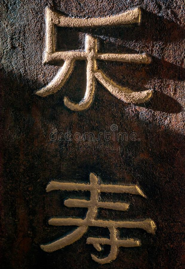 Chinese golden symbols on a brown background. With sun reflections royalty free stock image