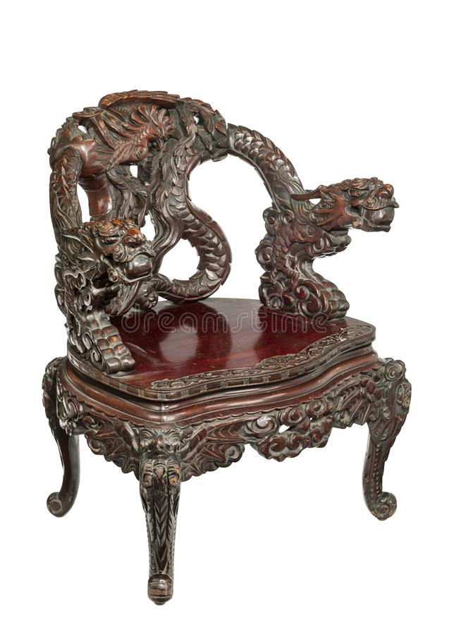 Chinese hardwood armchair with  carved with openwork designs. Highly carved Chinese rosewood arm chair, the arched back with relief carved dragon, curving arms royalty free stock photos
