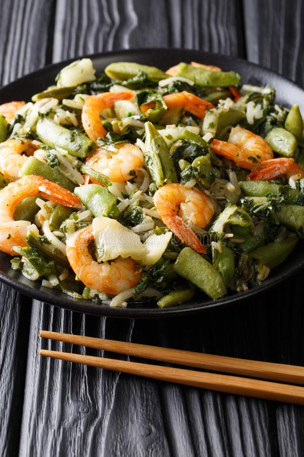 Chinese Healthy stir-fry of shrimp with spinach, soy sprouts, pe. As and pak choi close-up on a plate on the table. vertical stock photo
