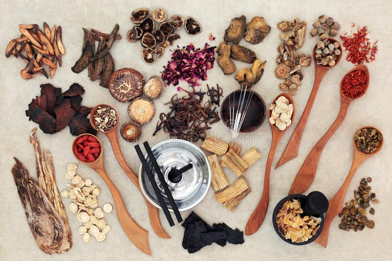 Chinese Herbal Medicine. With traditional herbs, acupuncture needles, moxa sticks used in moxibustion therapy and mortar with pestle on hemp paper background royalty free stock images