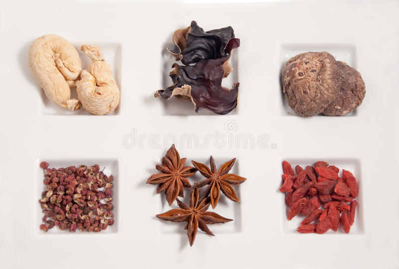Chinese herbs for cooking. Clockwise, l to r: gingseng, wood ear, shitake mushroom, szechuan pepper corn, star anise, dired medlar royalty free stock photo