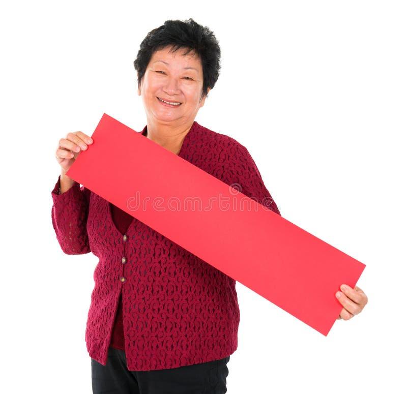 Chinese hogere vrouw met de rode lentecoupletten stock afbeeldingen