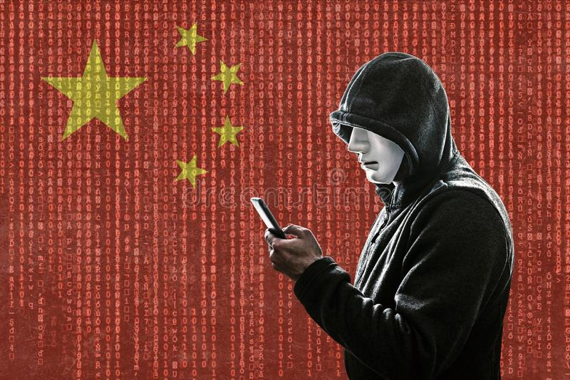 Chinese hooded hacker with mask holding smartphone stock images
