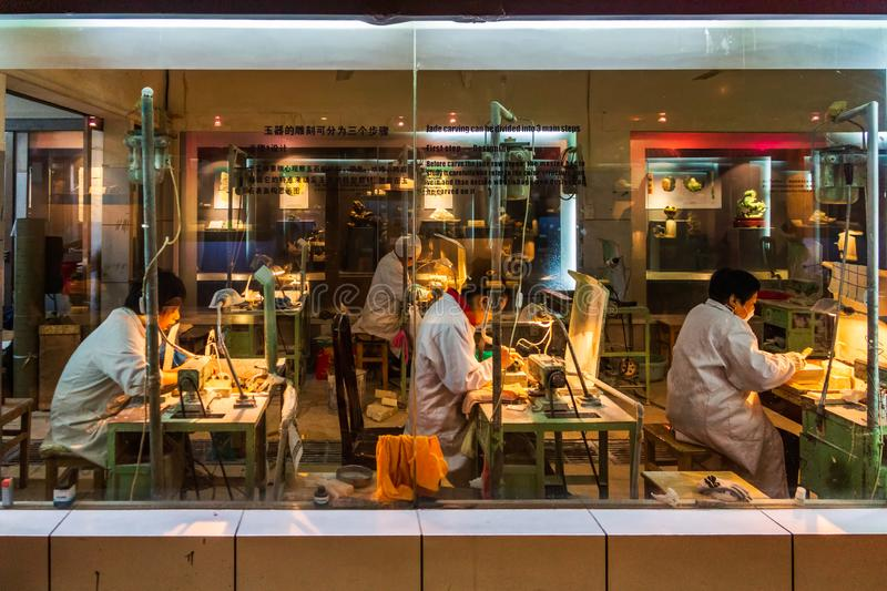 Chinese jade factory, group of workers are cutting jade into intricate patterns stock photo