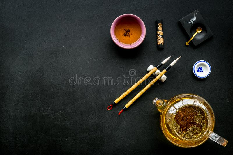 Chinese or japanese traditions. Calligraphy and tea ceremony concept. Special writting pen, ink near teapot and cup of. Tea, insense on black background top royalty free stock photo