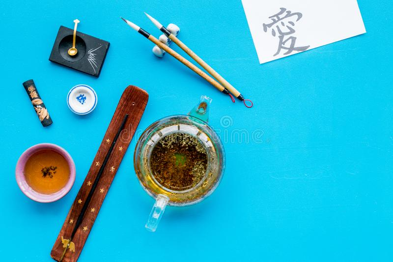 Chinese or japanese traditions. Calligraphy and tea ceremony concept. Special writting pen, ink near teapot and cup of. Tea, insense on blue background top view royalty free stock photo