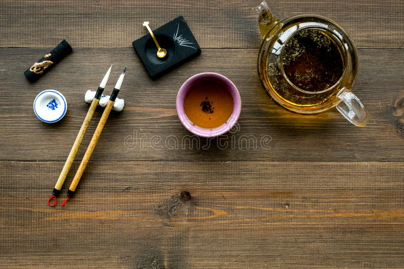 Chinese or japanese traditions. Calligraphy and tea ceremony concept. Special writting pen, ink near teapot and cup of. Tea, insense on dark wooden background stock image