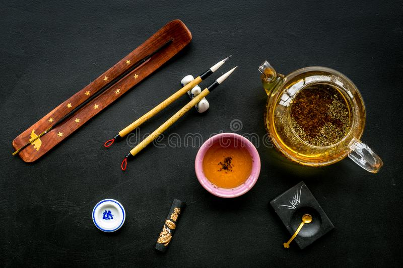 Chinese or japanese traditions. Calligraphy and tea ceremony concept. Special writting pen, ink near teapot and cup of. Tea, insense on black background top stock image