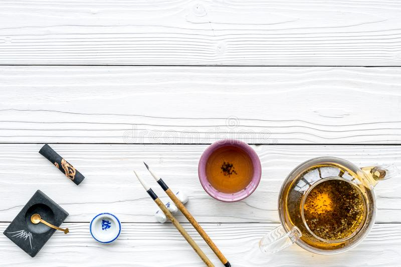 Chinese or japanese traditions. Calligraphy and tea ceremony concept. Special writting pen, ink near teapot and cup of. Tea on white wooden background top view stock photos