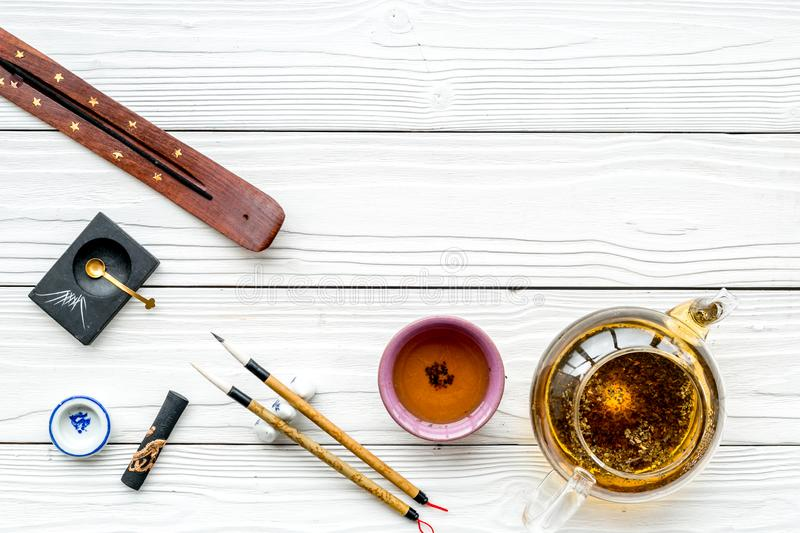 Chinese or japanese traditions. Calligraphy and tea ceremony concept. Special writting pen, ink near teapot and cup of. Tea on white wooden background top view royalty free stock photo