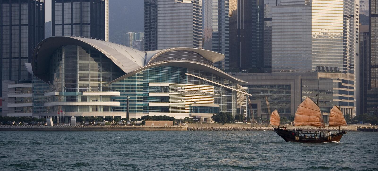 Chinese Junk in Hong Kong. Chinese Junk passing the Convention Center in Hong Kong Harbor royalty free stock photo