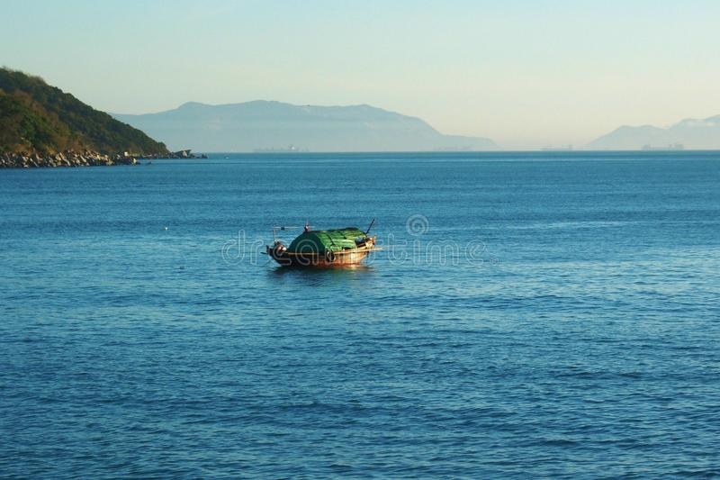 Chinese Junk Hong Kong Harbor. Small Chinese fishing boat with green cover in Hong Kong harbor with mountains in the background royalty free stock image