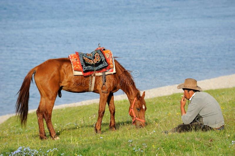 Chinese Kazakh herdsmen with horse at Sailimu lak royalty free stock images