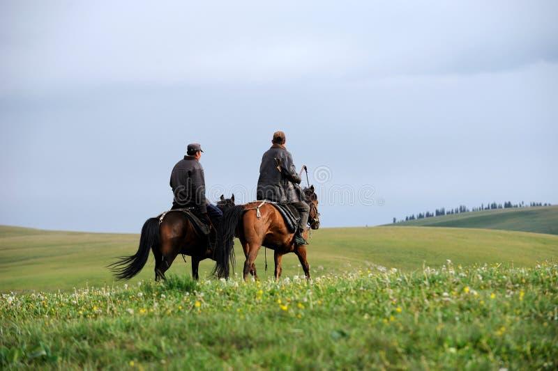 Chinese Kazakh herdsmen riding horse in grasslan royalty free stock photo