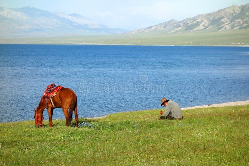 Chinese Kazakh veehoeders met paard bij Sailimu-meer stock afbeeldingen