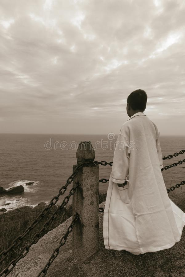 Chinese kid lookout sea wearing white robe royalty free stock images